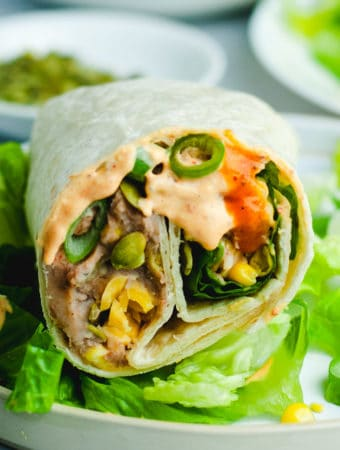Close up of bean burrito showing beans, queso, and corn. The burrito is sitting on a bed of romaine lettuce.