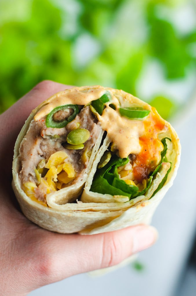 Hand holding a vegetarian bean burrito. The burrito is cut so that you can see the inside.
