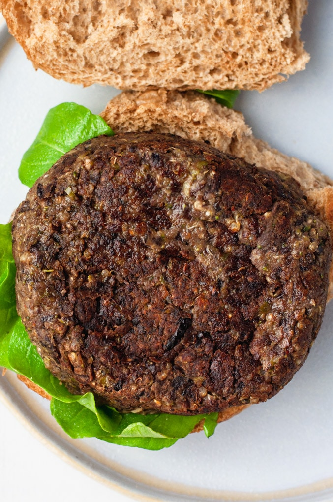 Overhead view of black bean burger patty resting on a bed of lettuce and whole wheat bun.