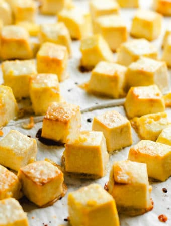 Golden brown cubes of tofu on parchment paper.