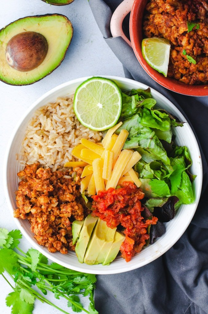 Overhead view of vegetarian burrito bowl ingredients in a large white bowl. An avocado and cilantro are in the background.