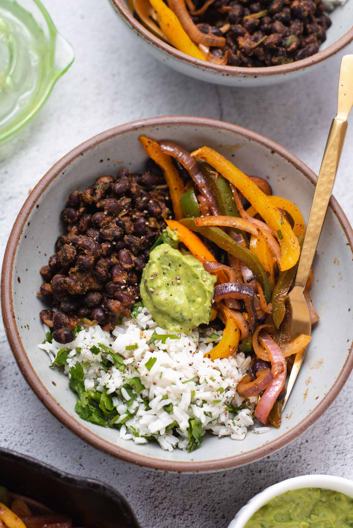 Overhead view of gray bowl filled with rice, fajita veggies, avocado cream and black beans