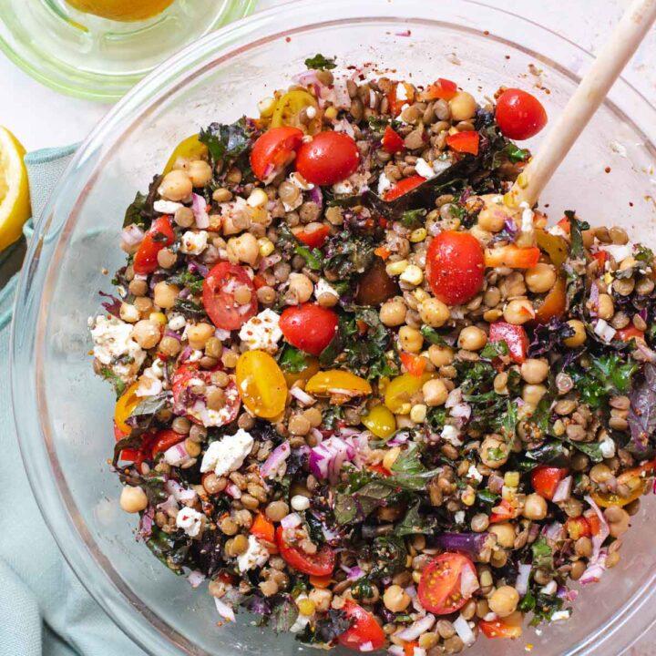 Large glass bowl filled with lentil salad on a blue cloth next to a lemon juicer