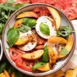 Overhead view of white bowl filled with peaches, tomatoes and basil