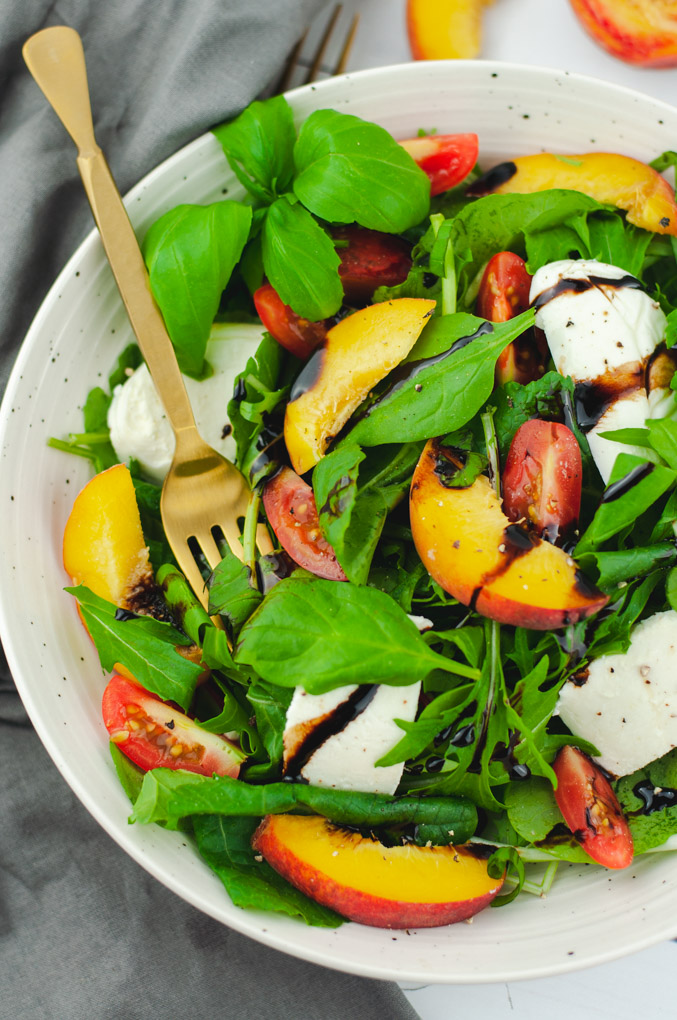 Gold fork resting on a green salad with peaches, mozzarella, and tomatoes