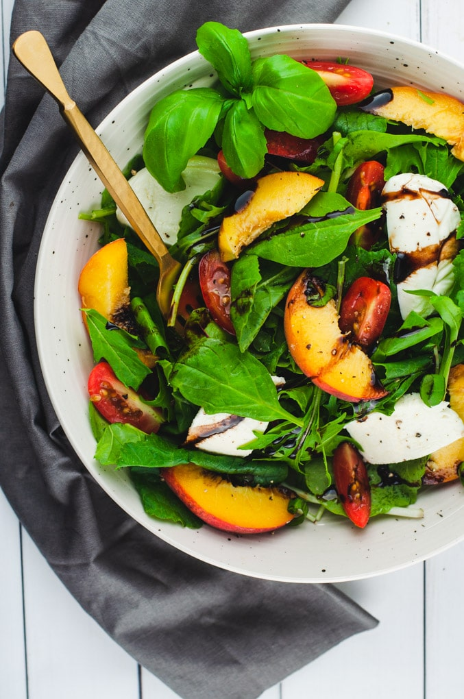 Overhead view of green salad with peaches, mozzarella, and sliced tomatoes on top.