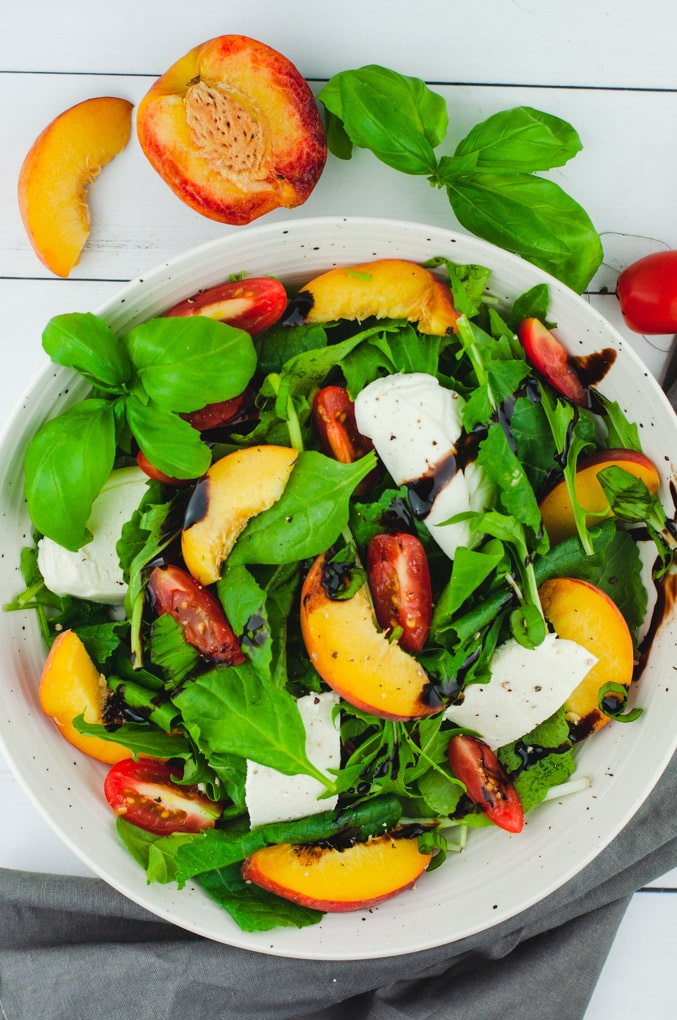 Overhead view of peach caprese salad on a white wood background. The salad is flanked by a whole peach, basil, and cherry tomatoes.