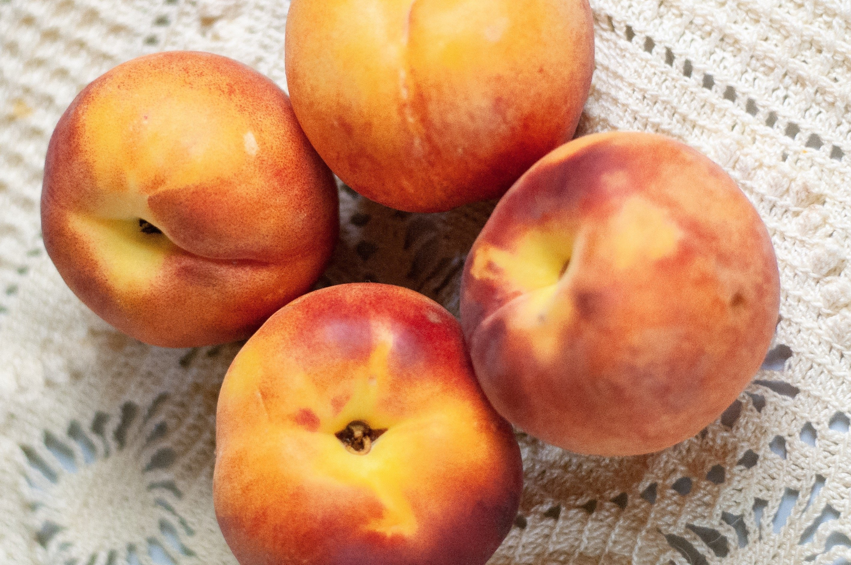 Four whole peaches resting on a beige background.