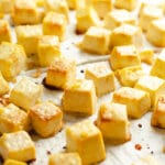 Golden cubes of tofu on parchment paper