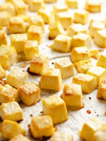 Golden cubes of tofu on parchment paper