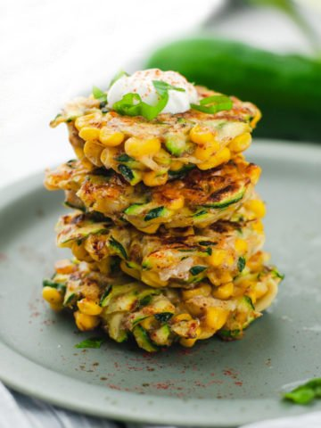 Four zucchini corn fritters stack on top of eachother. The top fritter has a dollop of Greek yogurt and basil.