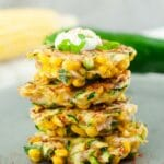 Four zucchini fritters stack on top of each other with a dollop of sour cream on top