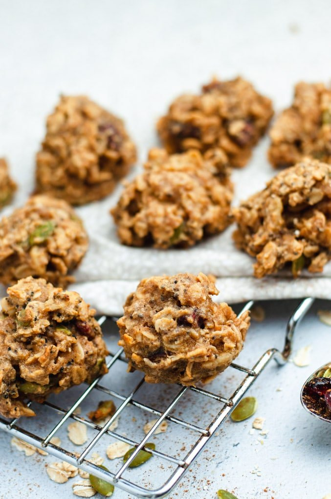 Eight vegan breakfast cookies on a metal cooling rack with a white cloth in the background.
