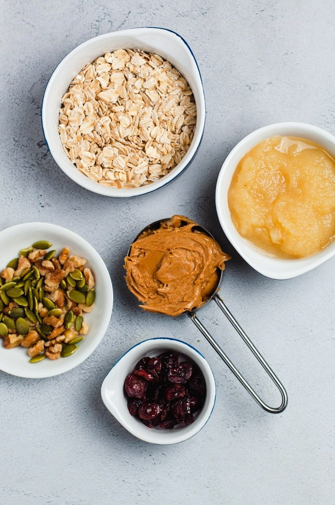 Ingredients used to make vegan breakfast cookies shown in separate bowls: oatmeal, applesauce, peanut butter, dry fruit, nuts and seeds.