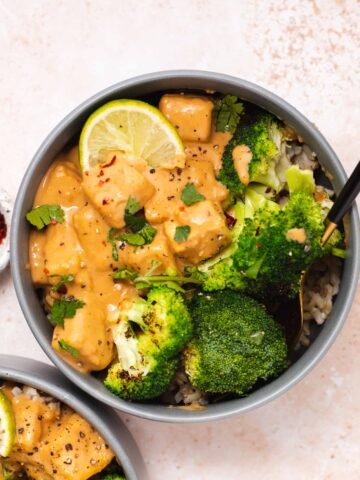 Overhead view of gray bowl with broccoli, peanut tofu and a lime wedge