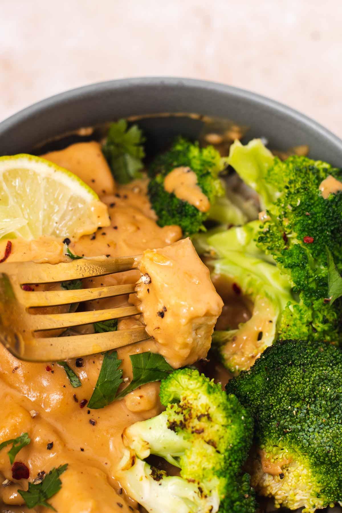 Gold fork piercing piece of peanut tofu