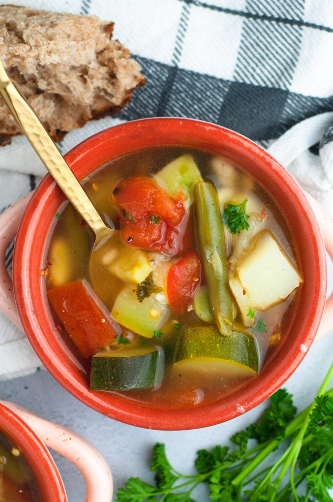 Red bowl with zucchini, squash and vegetables.