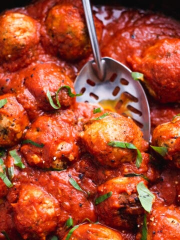 Close up of vegan meatballs in tomato sauce being lifted with a slotted spoon