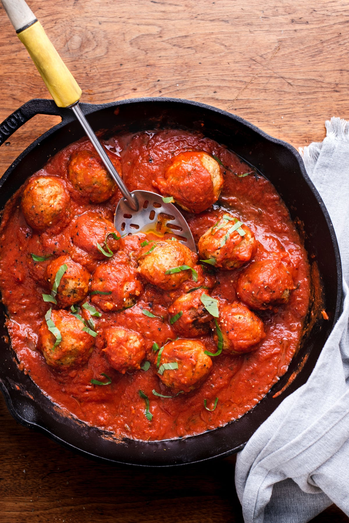 Overhead view of cast iron pan filled with meatballs in tomato sauce