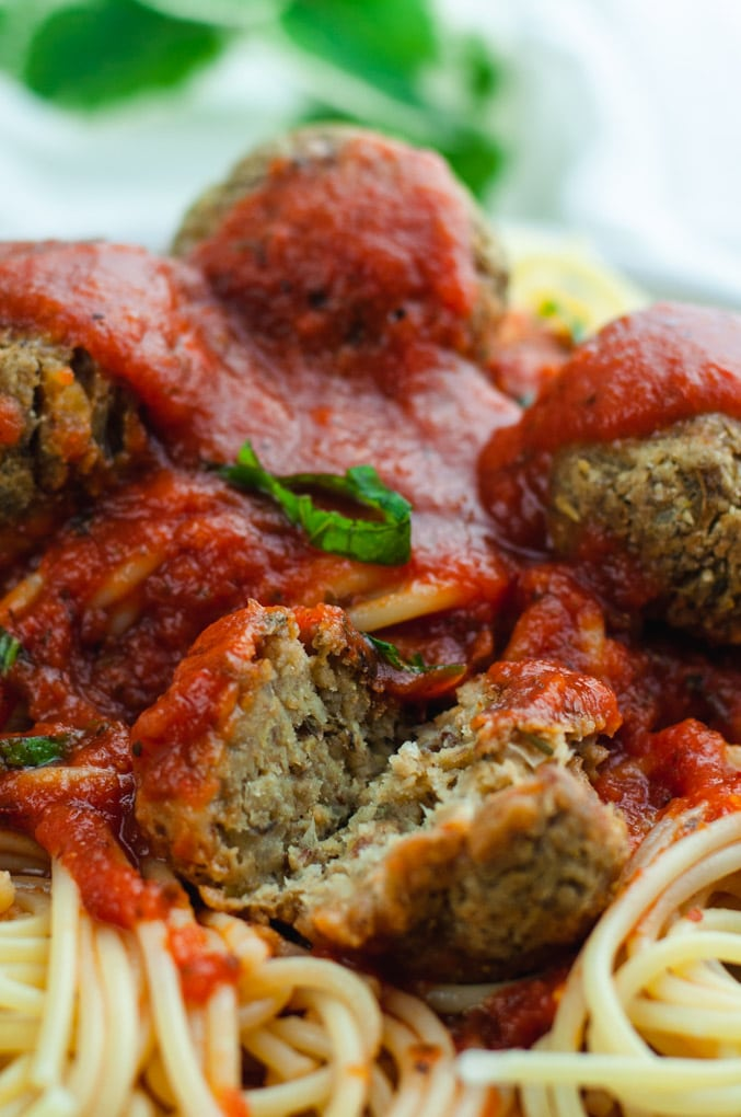 Meatball cut in half to show baked inside. The meatball is covered in red sauce and resting on spaghetti noodles.