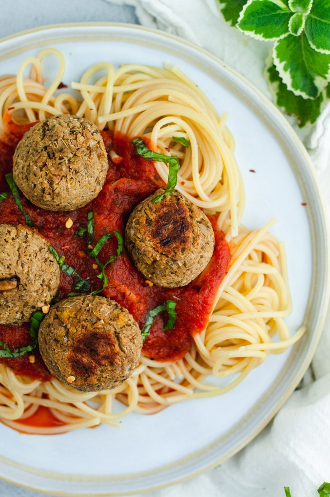 Overhead view of four brown vegan meatballs resting on top of spaghetti and tomato sauce.