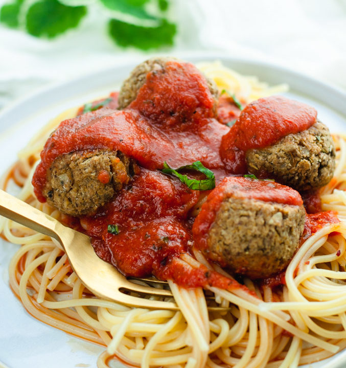 Gold fork poking a vegan meatball topped with red spaghetti sauce. The spaghetti and meatballs are on a white plate.