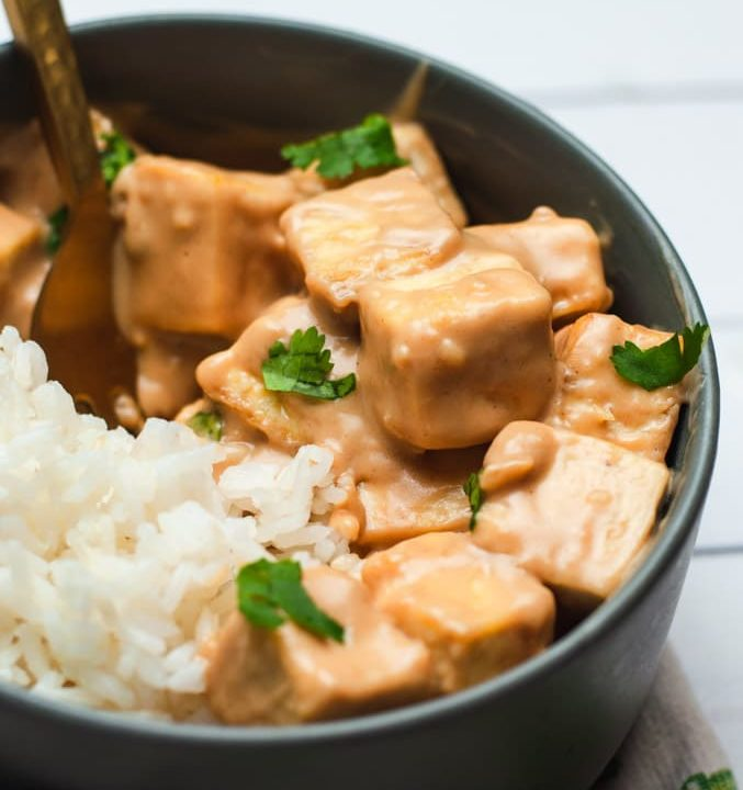 Close up view of cubes of tofu coated in a light brown peanut sauce. The tofu is in a gray bowl with white rice.