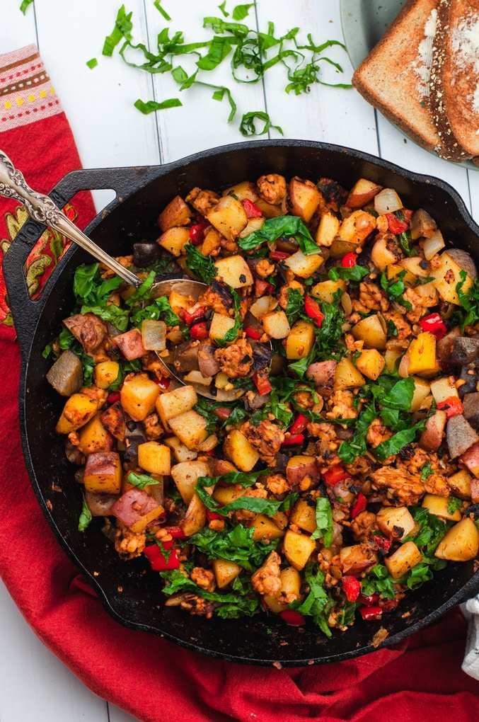 Potatoes, tempeh, and kale in a large cast iron skillet with a red clothe behind it.