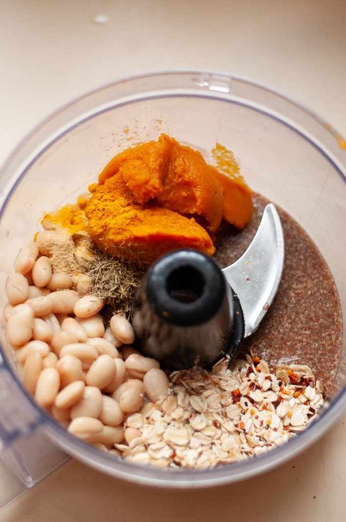 Food processor showing white beans, seasonings, pumpkin puree, flaxseed egg, and rolled oats.