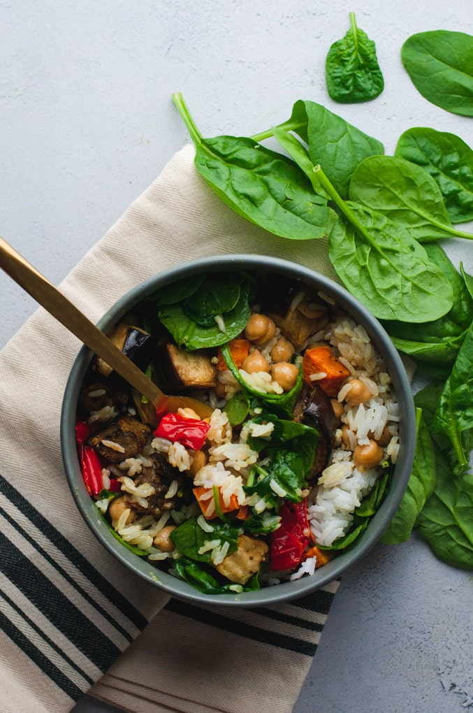 Overhead view of gray bowl filled with vegetables and rice on white cloth with spinach in the background