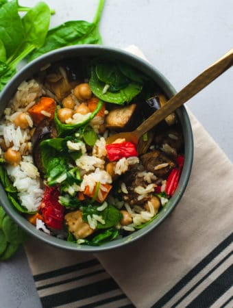 Coconut curry rice bowl in a gray bowl with fresh spinach in the background.