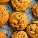 Orange colored pumpkin cookies lined up on a metal wire baking rack.