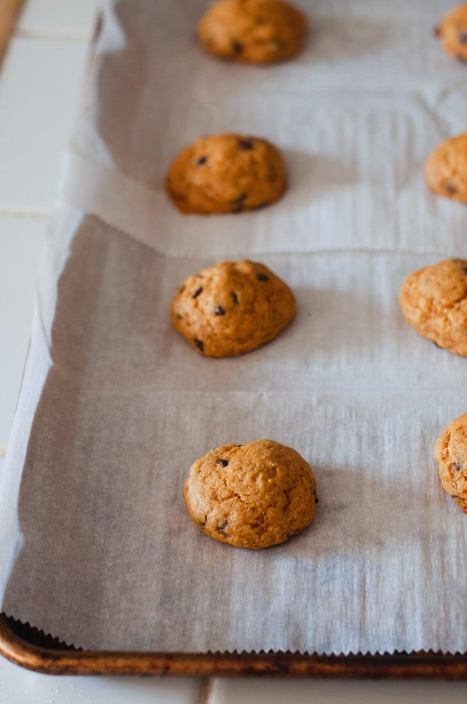 Pumpkin chocolate chip cookies on a white parchment paper lined baking sheet.