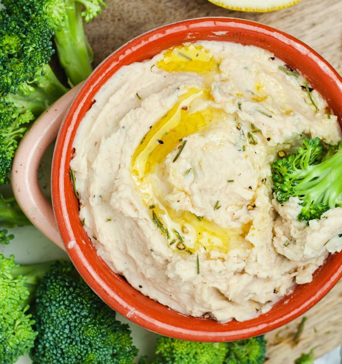 Close up overhead view of white bean dip in an orange bowl.