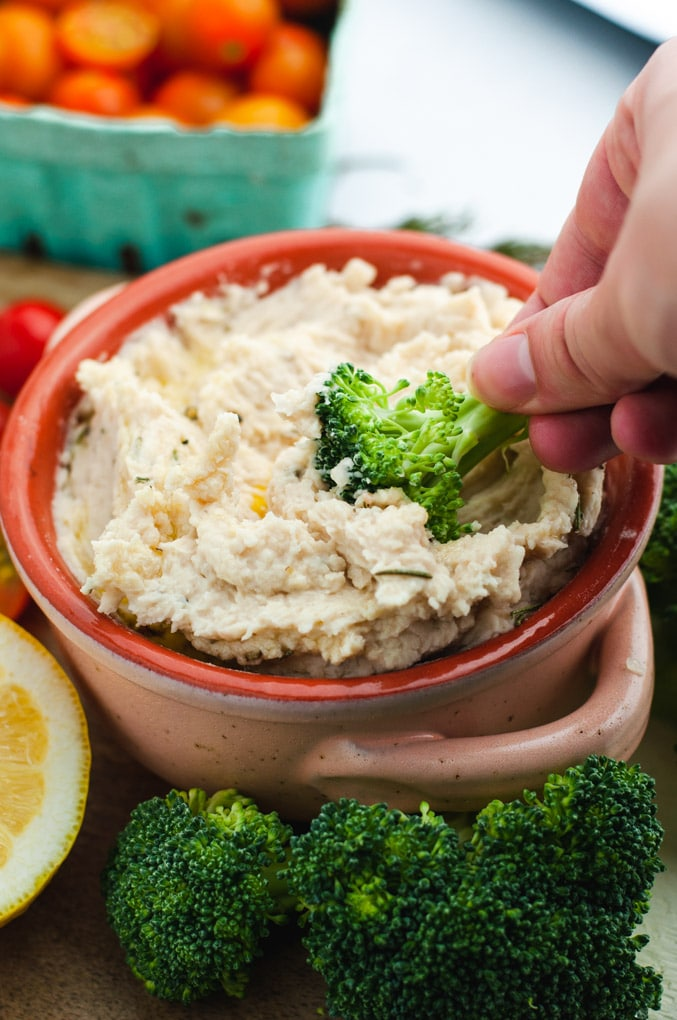 Piece of broccoli being dipped into white bean dip.
