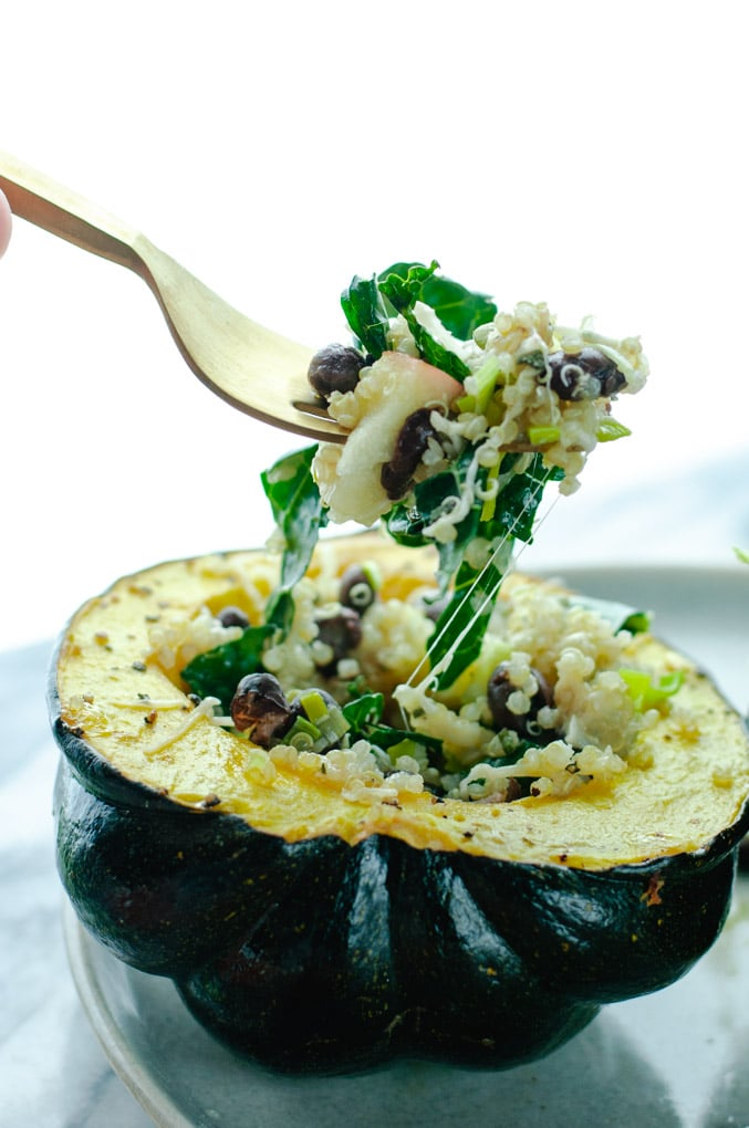 Gold fork lifting a bite of quinoa and kale out of roasted stuffed squash.