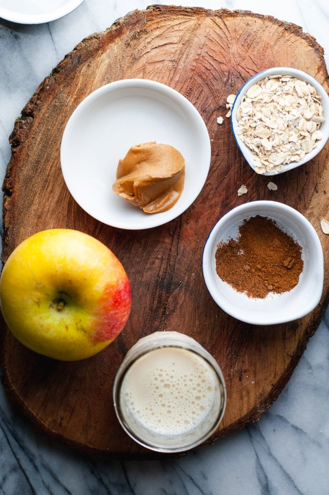Ingredients used to make apple cinnamon smoothies sitting on a wooden slab and marble background.