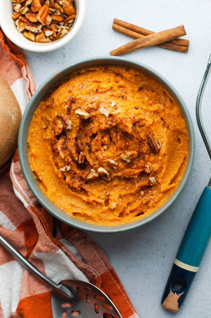 Large dark gray bowl filled with mashed sweet potatoes. The bowl is on a gray background with utensils and ingredients lying around it.