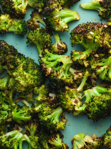 Close up of detail of roasted garlic broccoli on a blue sheet pan.