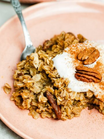 One serving of pecan baked oatmeal on a pink plate topped with yogurt and pecans