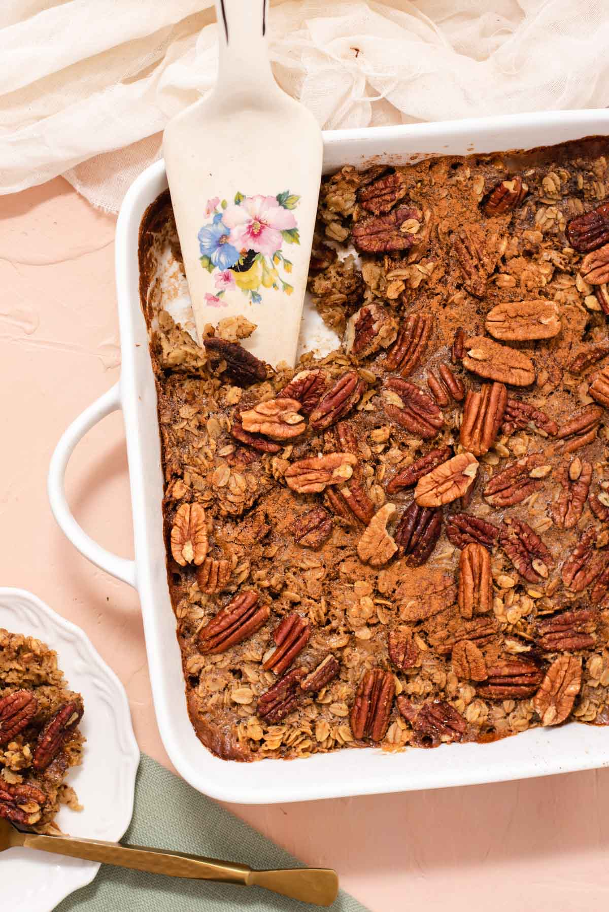 White square baking dish filled with pecan baked oatmeal and a white pie server