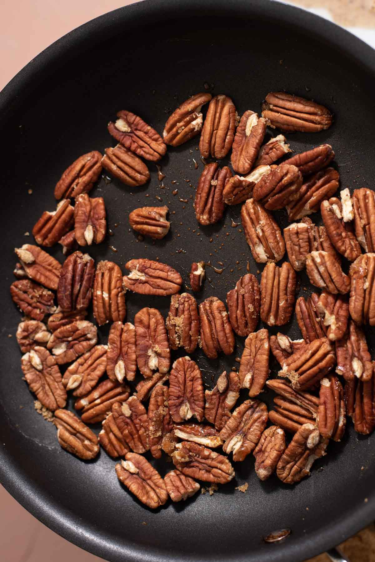 Whole pecans toasting in a black skillet