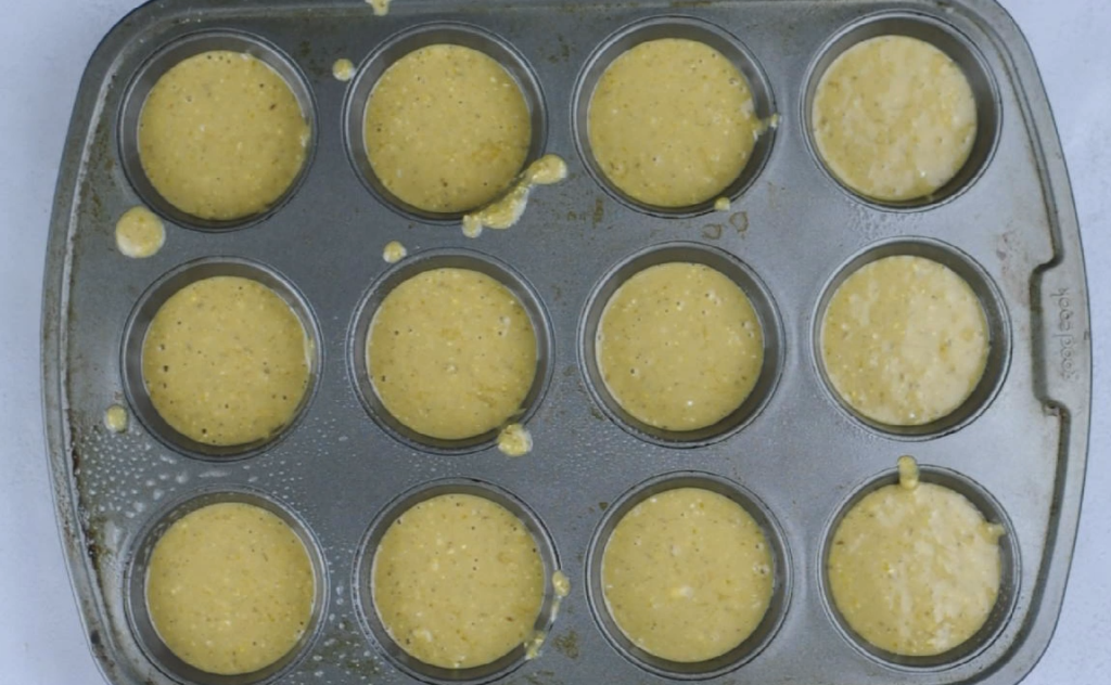Metal muffin tins filled with cornbread muffin batter
