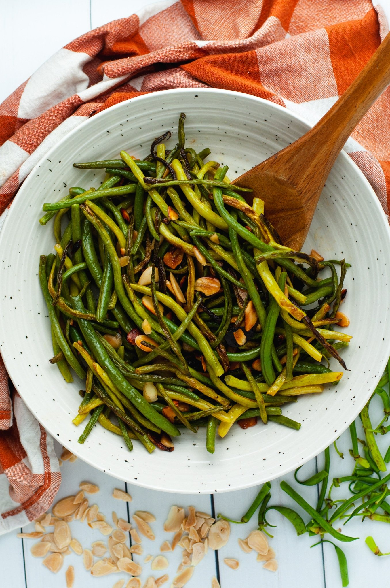 Overhead view of green beans almondine in a white bowl on an orange linen
