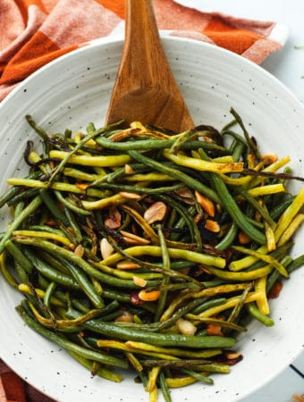 One recipe of green beans almondine in a white ceramic bowl with a wooden serving spoon