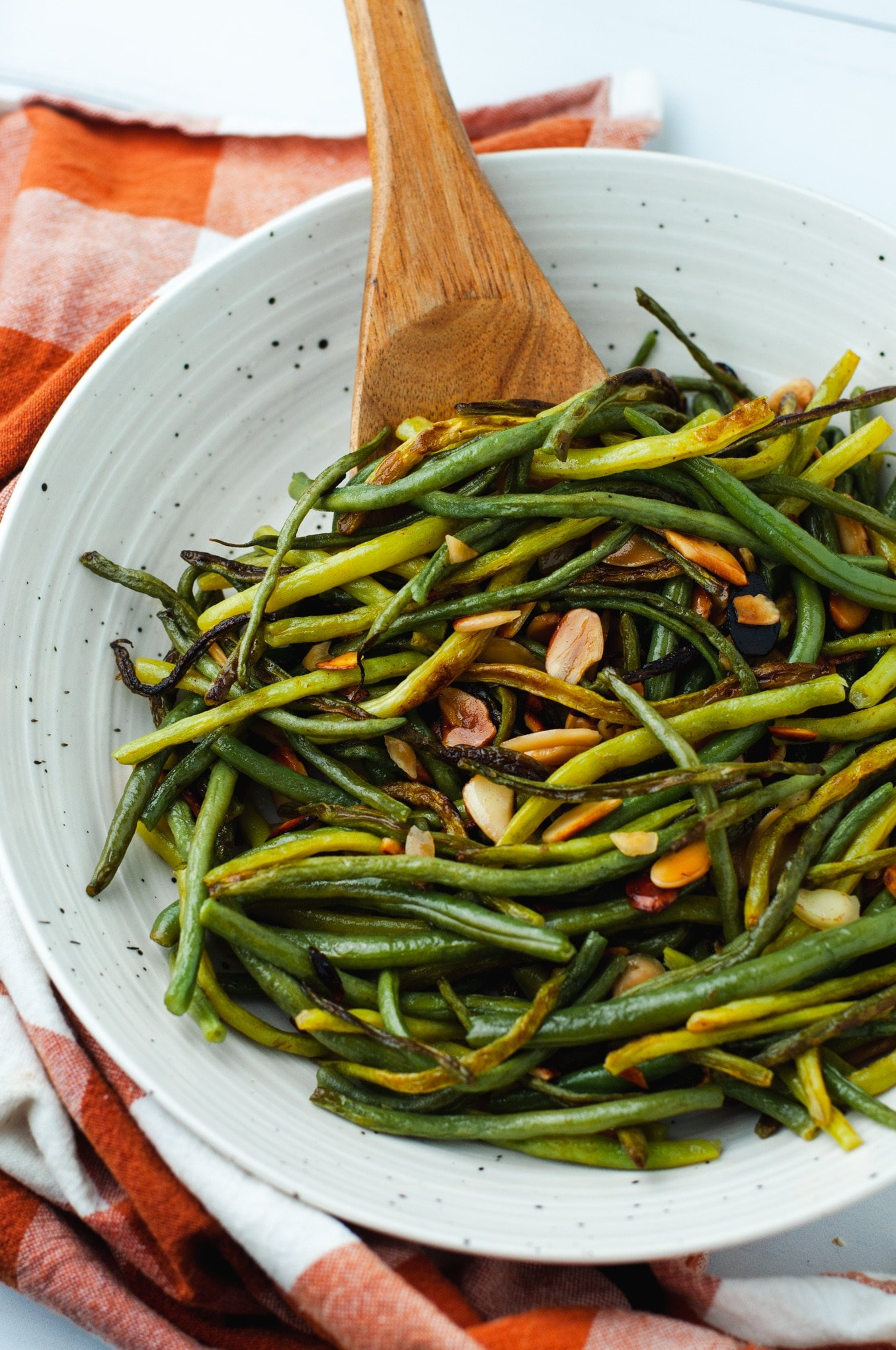 Green beans almondine in a white ceramic bowl with a wooden serving spoon