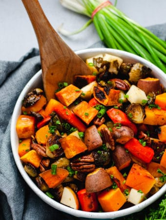 Wooden spoon resting in a bowl of roasted root vegetables with green onions and parsley in the background