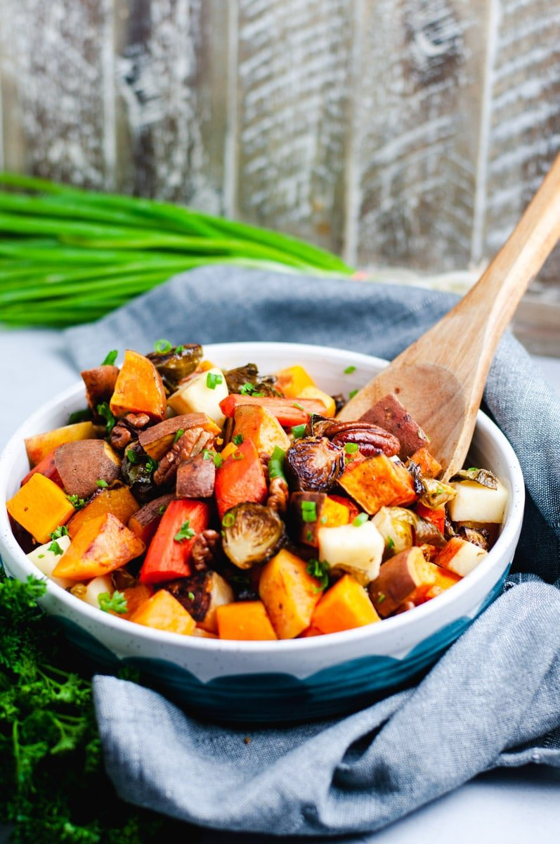 Roasted sweet potato and butternut squash in a white and blue bowl with a wooden spoon