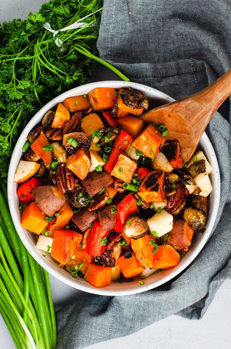 Overhead view of roasted root vegetables in a white bowl on a gray linen cloth. Green onions and parsley surround the bowl.
