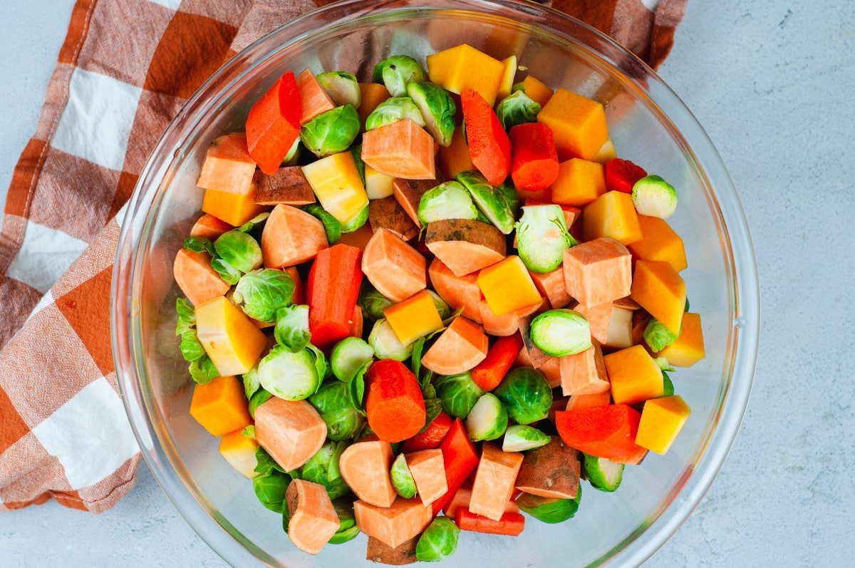 Diced and uncooked sweet potato, brussel sprouts, butternut squash and carrots in a large glass bowl